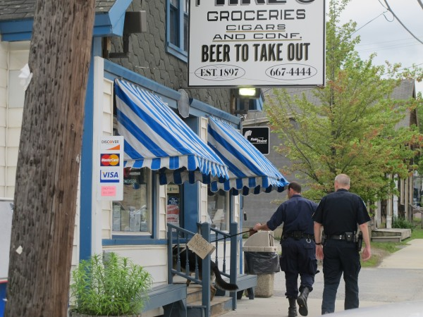 Ellsworth police officer and a police dog search the area around Mike's Country Store after an alleged robbery on Sunday afternoon.