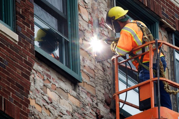 A workman welds metal between the fifth and sixth floors above 142 High Street in Portland Monday afternoon where part of the brick facade separated from the building on Sunday.