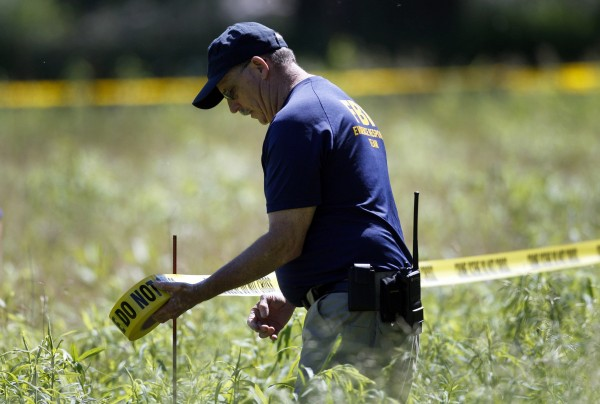 A federal agent stretches yellow crime tape around a field which investigators are prepared to dig up for the remains of former Teamsters boss Jimmy Hoffa, in Oakland Township, Michigan June 17, 2013. The latest search for Hoffa, who disappeared in 1975 in what law enforcement officials believe might have been an organized crime hit, brought investigators on Monday to an overgrown vacant field in suburban Detroit.