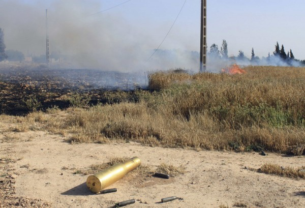 An empty ammunition casing and a fire are seen in a field after heavy fighting between Free Syrian Army fighters, and the forces of Syrian President Bashar al-Assad and Lebanon's Hezbollah at the al Barak area near Qusair town May 31, 2013.