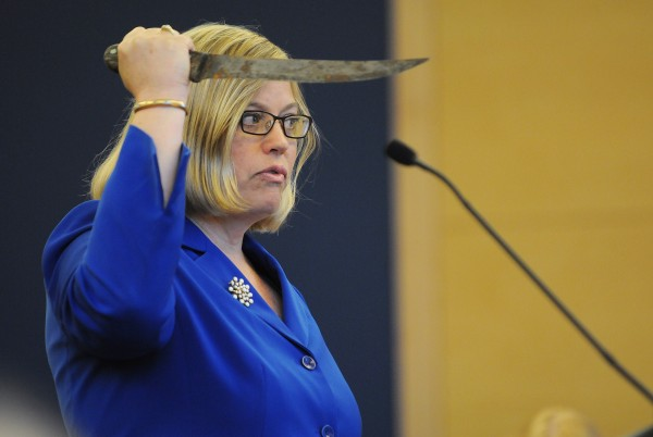 Assistant District Attorney Alice Clifford demonstrates to the jury, during opening arguments on Monday at the Penobscot Judicial Center in Bangor, how the prosecution claims Warren Dome threatened state police with a knife on August 14, 2012, at his home in Edinburg.