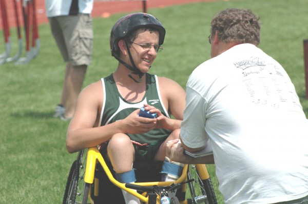 Fort Kent High School senior Robbie Hebert is interviewed by Bangor Daily News reporter Ernie Clark after Hebert competed in his wheelchair in the 100 meters, 400 meters and shot put at the Class C track state meet Saturday in Dover-Foxcroft.