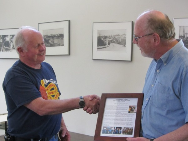 Retiring Rockport Fire Chief Bruce Woodward (left) is handed a framed copy of the town's annual report that was dedicated to him on Friday afternoon. The report was presented by Rockport Selectman Bill Chapman.