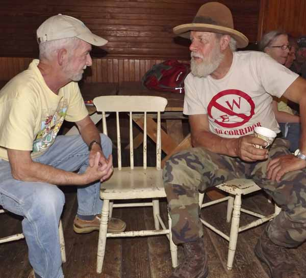 Jim Roberts of Dover-Foxcroft, left, discusses the East-West Highway proposal with Harry Akkermann of Harmony at the June 21 forum hosted by the East Sangerville Grange.