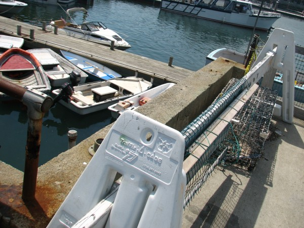 A temporary barricade and a old lobster trap block off the edge of the Bar Harbor Town Pier where part of a railing is missing on Friday, May 31, 2013. The town plans to remove the existing railing and knee wall and to replace them sometime in 2014.