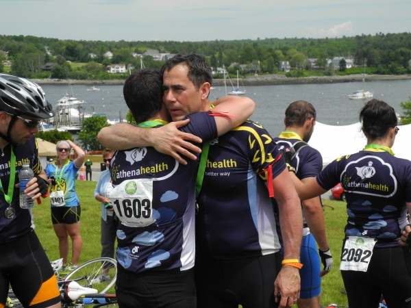 David Tassoni of athenahealth embraces a teammate after finishing the three-day, 180-mile Trek Across Maine on Sunday afternoon. David LeClair, a 23-year-old athenahealth employee from Watertown, Mass., was killed Friday morning shortly after the beginning of the fundraising event in a collision with a tractor-trailer truck. &quotI'm so proud of being part of this whole group,&quot Tassoni said at the trek's emotional conclusion.