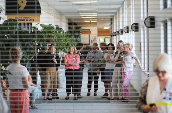 Employees in the EMMC Healthcare Mall watch through a metal gate as a mock disaster drill unfolds in their building on Union Street in Bangor on Tuesday.  Numerous law enforcement and rescue departments took part in a planned community-wide emergency preparedness drill.