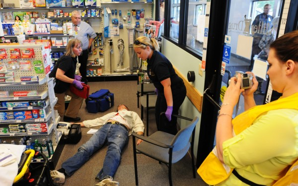 First responders attend to a volunteer victim at Miller Drug Westgate at the EMMC Healthcare Mall on Union Street in Bangor on Tuesday as Eastern Maine Health Care employee Shannon Dobbins, right, takes pictures. Numerous law enforcement and rescue departments took part in a planned community-wide emergency preparedness drill.