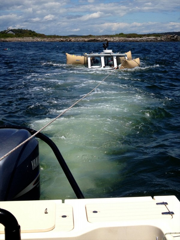 The refloated Queen Tut is towed back to the dock Sunday afternoon in Harpswell after sinking Saturday with 90-year-old Philip Tuttle aboard. He was forced to swim to nearby rocks using his display lobster buoy as a flotation device.