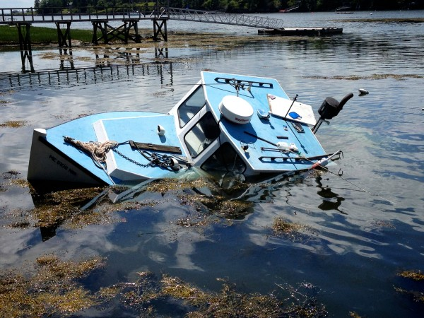The Queen Tut sits in the shallows Sunday afternoon in Harpswell as the tide goes out. The boat sank Saturday with 90-year-old Philip Tuttle aboard. He was forced to swim to nearby rocks using his display lobster buoy as a flotation device.