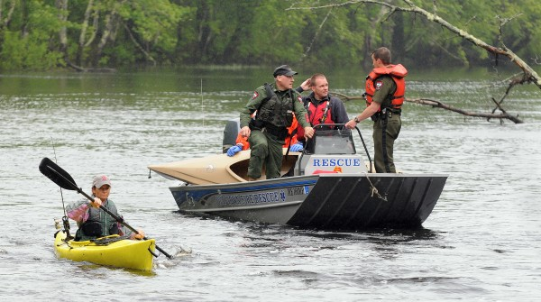 Orono rescue personnel and game wardens bring a kayak belonging to Melissa McLaughlin back to shore after rescuing the Brewer resident from Pushaw Stream on Wednesday.