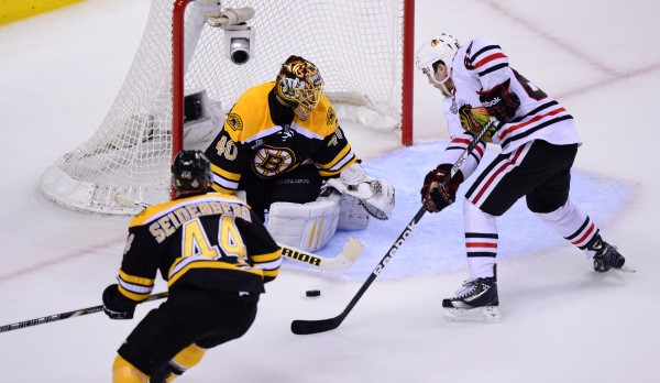 Boston Bruins defenseman Dennis Seidenberg (44) watches as goalie Tuukka Rask (40) makes a save against Chicago Blackhawks center Andrew Shaw during the third period in Game 3 of the Stanley Cup Finals at TD Garden in Boston Monday night.