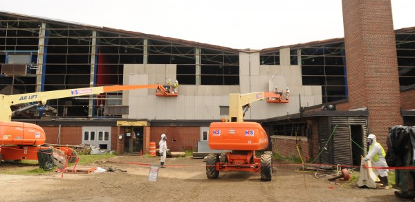 Workers remove asbestos panels from the girders of the Bangor Auditorium exposing the interior to the outdoor elements on June 6, 2013. The defunct community facility in Bangor is being dismantled and is expected to take 6 weeks to compete.