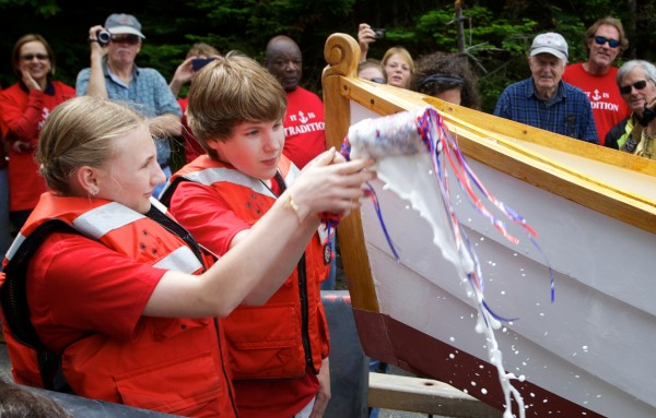 South Bristol School eighth-graders Jordan Farrin and Tyler Giles christen a skiff before it is launched in South Bristol on Friday. The pair, along with their classmates, made the boat over the course of the school year at the Maine Maritime Museum's boat shop.