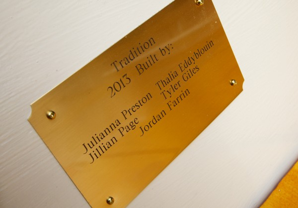 A plaque on a skiff named Tradition bears the names of its eighth-grade shipbuilders as it is launched Friday in South Bristol.