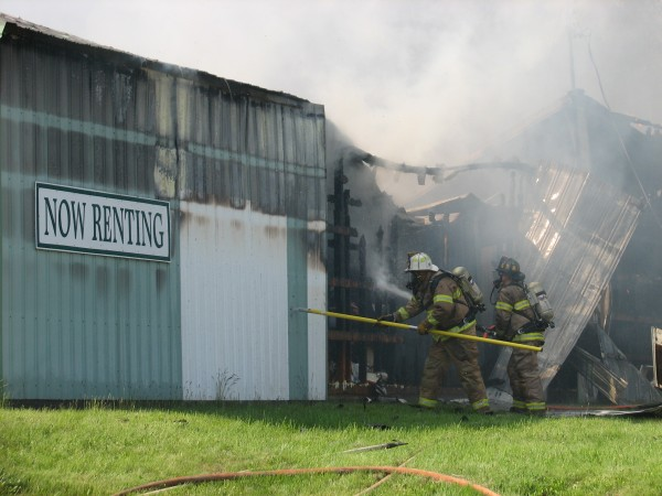 Firefighters pull away metal sheathing and spray water inside a storage rental unit building on Route 172 in Sedgwick on Saturday.