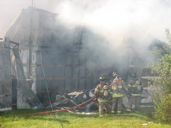 Firefighters spray water inside a smoldering shell of a storage rental unit building on Route 172 in Sedgwick on Saturday, June 1, 2013.