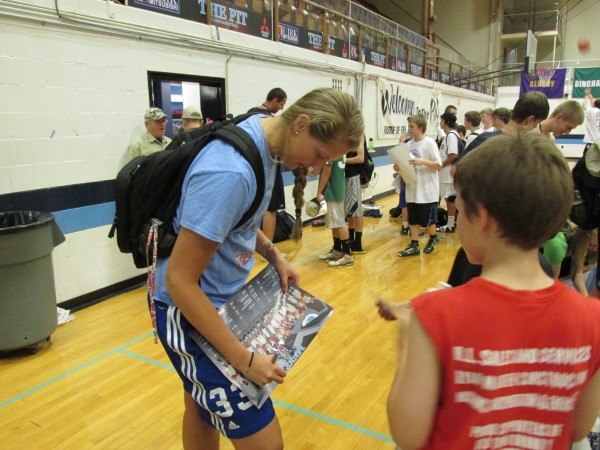 Ali Nalivaika of the University of Maine women's basketball team signs an autograph for a youngster Thursday upon completion of a boys basketball summer camp at Memorial Gym in Orono. The junior center is among numerous Black Bear athletes who are spending most of the summer on campus.