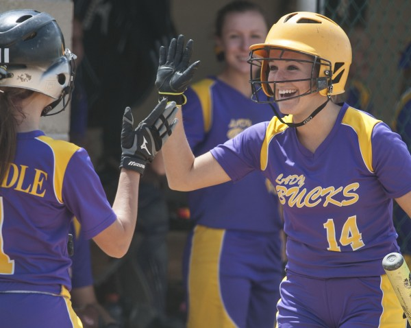 Bucksport High School softball player Brianna Bires (14) congratulates teammate Kaylee Grindle (1) for reaching home in the sixth inning  of their championship game against Madison Area Memorial High School in Brewer, Maine Saturday, June 15, 2013.