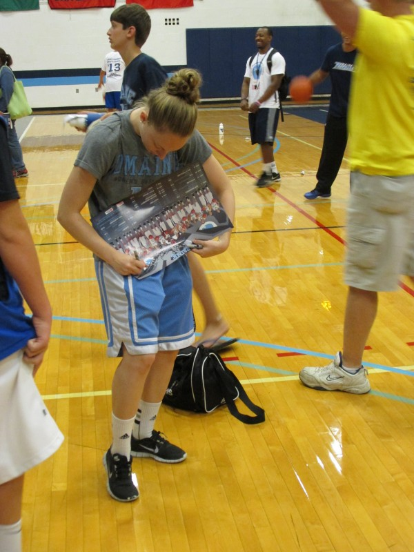 Courtney Anderson of the University of Maine signs an autograph for a player on Thursday at a boys basketball camp at Memorial Gym in Orono. Black Bear student-athletes often stay on campus during the summer to study and train for their sports.