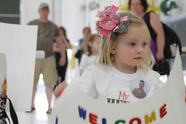 Ariana Poulin holds up a sign Saturday for her father's return from Afghanistan.