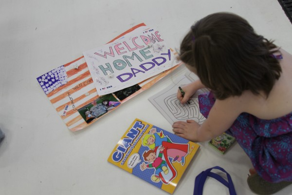 Ariana Priest puts some final touches to her sign welcoming home her father, Aaron Priest, from his final deployment.