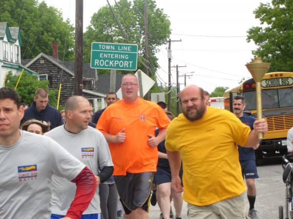 Ryan Bidal holds the torch as runners reach the Rockland town line from Rockport on Wednesday morning, June 6, 2012. The annual Law Enforcement Torch Run to benefit Maine Special Olympics kicked off again Tuesday, June 4, in Sanford.