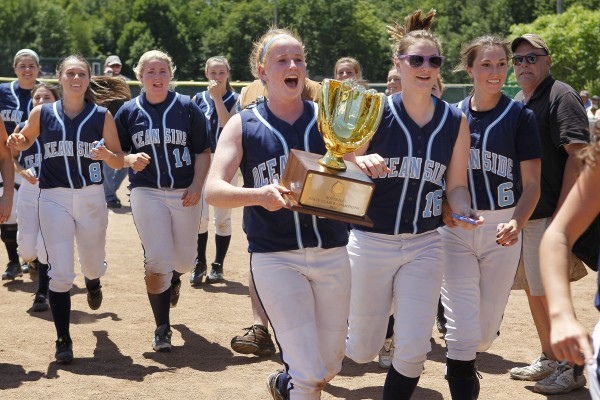 Oceanside shortstop Molly Mellor leads her  Mariners teammates in a celebration with the Class B softball state championship trophy after defeating Greely in Standish.