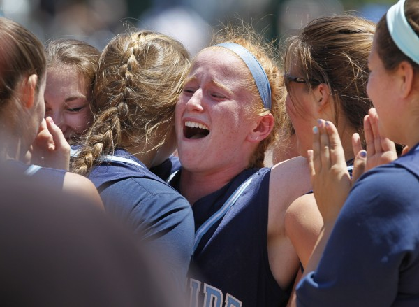 Oceanside shortstop Molly Mellor, center, celebrates with teammates after the Mariners won the Class B softball state championship in Standish.