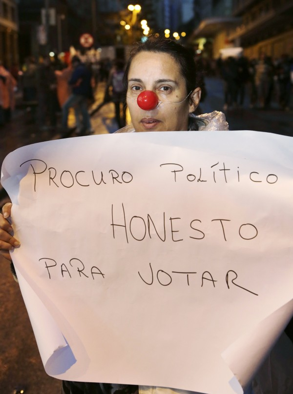 A demonstrator holds a sign during a protest in Porto Alegre.June 24, 2013. Brazilian President Dilma Rousseff on Monday proposed a popular referendum to embark on a sweeping political reform in response to the country's largest public protests in 20 years.
