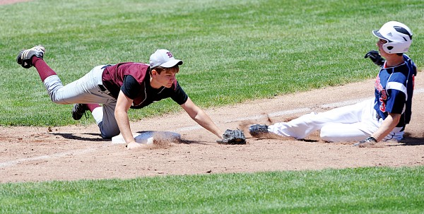 Buckfield's Owen Bennett dives for the ball as Bangor Christian's Cody Collins slides into third base early in the Class D State Championship game in Standish Saturday. Collins was out after Bennett was able to just barely make the tag, however the Patriots went on to win 4-0.