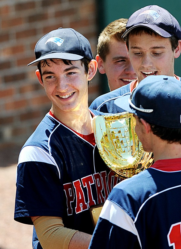 Bangor Christian's Cody Collins is all smiles as he cradles the golden glove trophy after his team won the Class D State Championship in Standish Saturday. The Patriots triumphed 4-0 over the Buckfield Bucks.