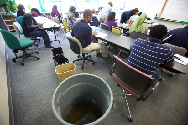 Students attend class at Portland Adult Education on Wednesday as rainwater from the roof drips into three different trash cans.