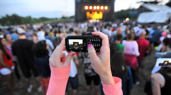 McKenna Gibbs takes a picture with her phone as Rodney Atkins starts playing at the Bangor Waterfront on Friday evening. Atkins opened for Darius Rucker.
