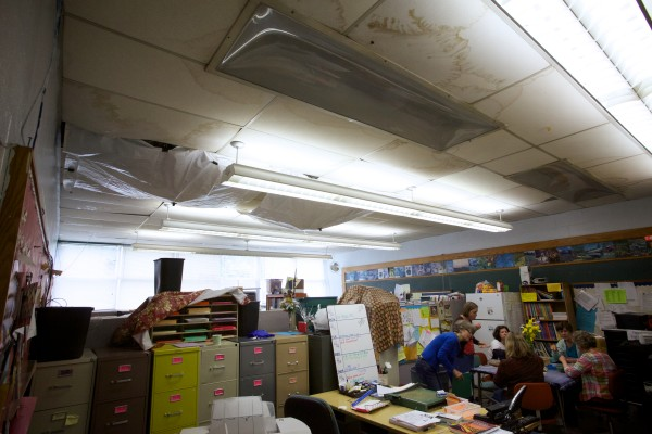 Teachers congregate in the staff room at Portland Adult Education on Wednesday under a ceiling scarred by leak stains and plastic sheeting directing rainwater into buckets and trash bins.