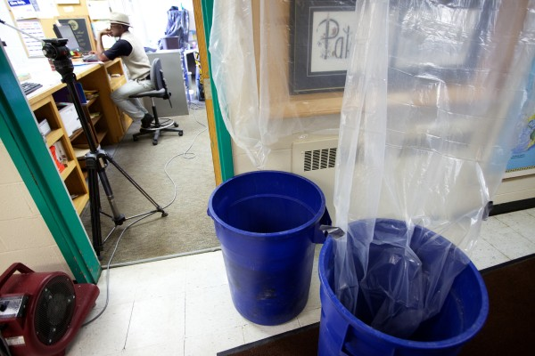 Willy Katihabwa works in the office at Portland Adult Education on Wednesday amid plastic sheeting a barrels collecting rainwater that percolates through the roof.
