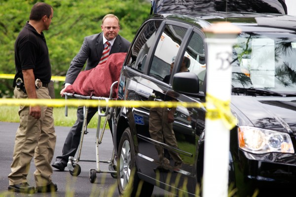 Officials on the scene remove one of two bodies from 53 Durham Road in Freeport Tuesday.