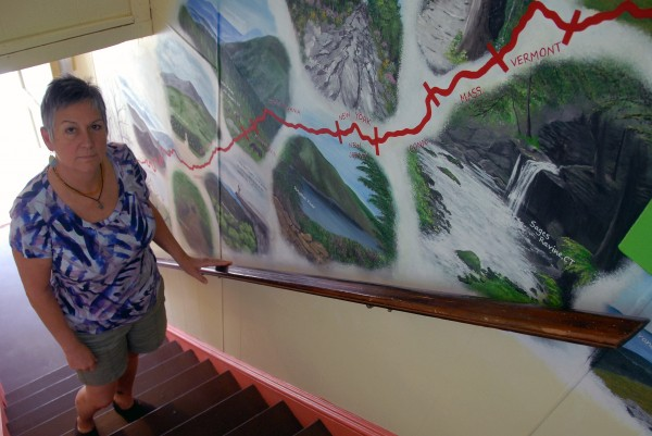 Millinocket Appalachian Trail Committee member Jaime Renaud, standing near a mural of the trail, says that the town's recent designation as a national Appalachian Trail Community will bring tourism dollars into the Katahdin region.