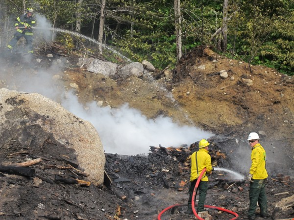 Firefighters from Dedham and Ellsworth work to knock down a brush fire that had gotten out of control at a construction company site in Dedham on Tuesday.