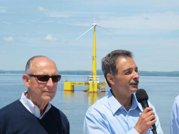 Habib Dagher, right, director of UMaine's Advanced Structures and Composites Center, speaks to a crowd of journalists aboard a Maine Maritime Academy research ship Thursday in Castine Harbor. At left is Peter Vigue, CEO of Cianbro Corporation, which partnered with the university to create the one-eighth scale VolturnUS floating wind turbine, in background.