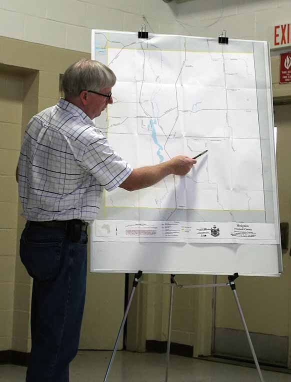 Hodgdon Town Manager Jim Griffin points out a section of road to be closed on a map during a special town meeting Monday. About 100 residents turned out for the meeting.