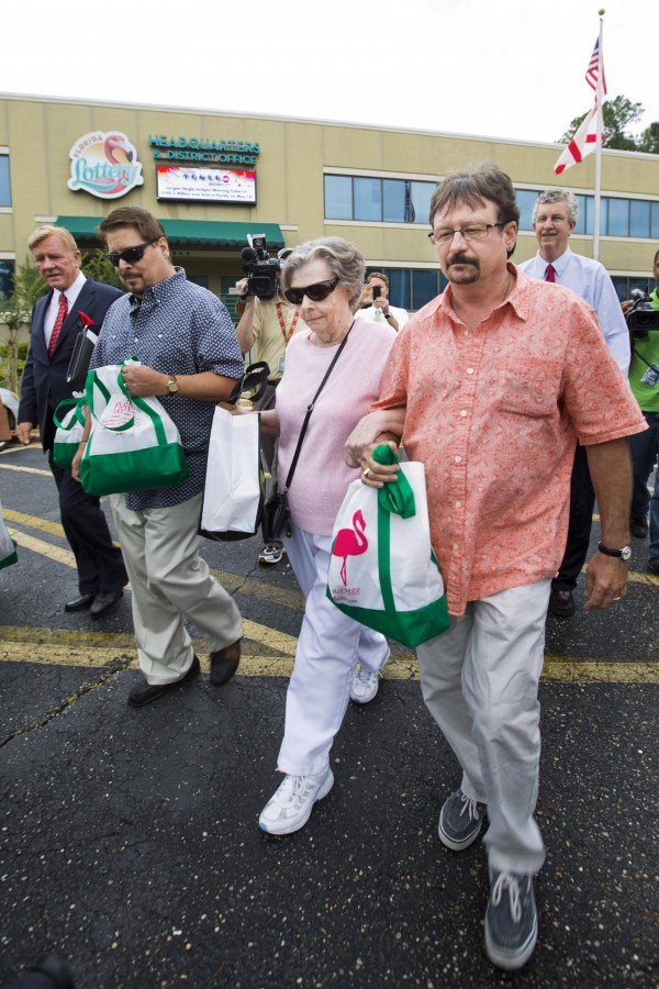 Gloria C. Mackenzie, an 84-year-old woman from Zephyrhills, Florida (C), her son Scott (R) and a person identified by Lottery Officials as &quota trusted family friend&quot (L) leave the Florida Lottery offices after claiming the largest single Powerball jackpot in American lottery history, valued at $590 million.
