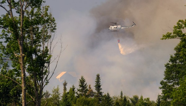 A helicopter drops water on an intense forest fire in Newburgh Tuesday afternoon.
