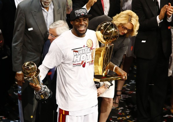 Miami Heat small forward LeBron James celebrates with the Larry O'Brien Championship trophy and the MVP trophy after Game 7 in the NBA Finals at American Airlines Arena. Miami defeated San Antonio 95-88 to win the title Thursday night.