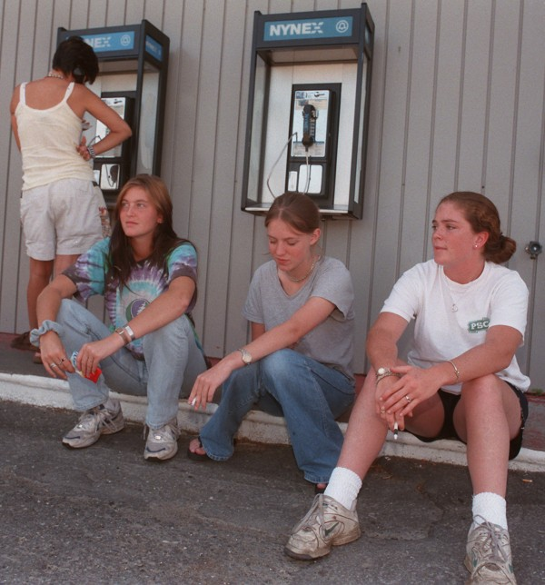 Kelley Somerville, Caroline Stoddart and Colleen Quinn, all of Rye, N.Y., anxiously await a call outside of the Old Town Western Union Office in August 1997. They had lost all their money when Kelley's wallet was left on top of the car at their last gas stop in southern Maine. She hoped her father would wire money so they could continue to Limestone.