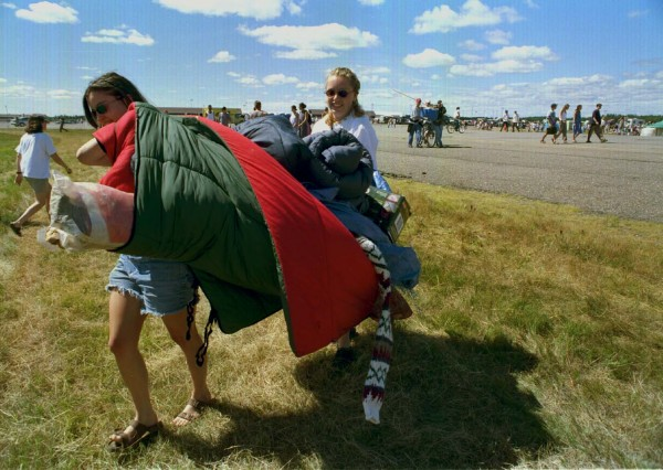 Carrying all their needs for the weekend, first-time Phish phans (from left) Jen Brown, 19, and Ellen Crowley, 20, both from the Boston area, make their way to the tenting area  in August 1997.