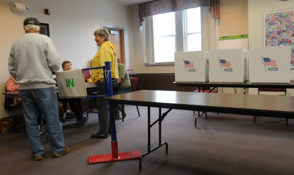 John and Colleen Robbins chat with elections clerks before casting votes in Orono on Tuesday.