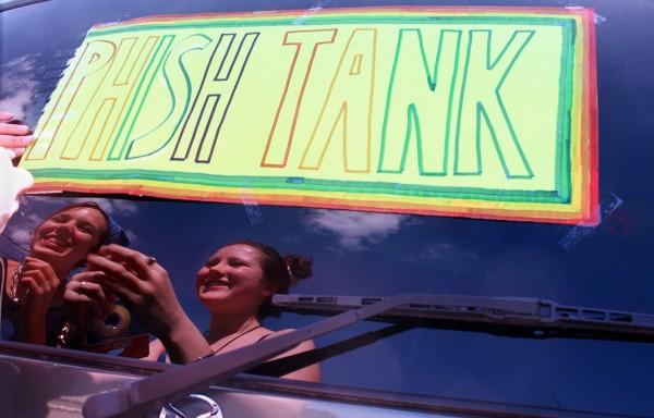 Erin Stanton (left) and Brenna Sharp tape a Phish Tank sign to the back of a rental vehicle in August 1998 at Dysart's parking lot in Hermon. The fans from Ellenville, N.Y., spent the previous night in Bangor after their minibus broke down.