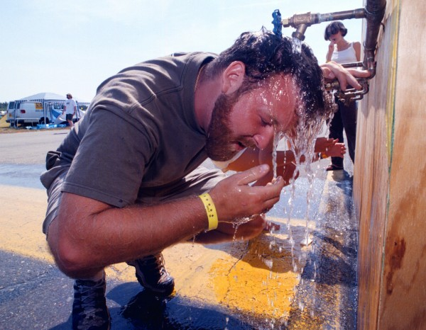 Dan Dumas of Cape Cod cools off under a portable water faucet being supplied in the campgrounds at Loring Commerce Centre in August 1998.