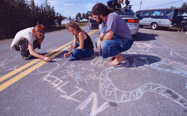 Matt Merlin, Beene Hendricks and Colin Brown create chalk art on the pavement of Corrow Road Thursday as they waited for the east gate of Loring Commerce Centre to open that morning for Phish's Lemonwheel concert in August 1998.